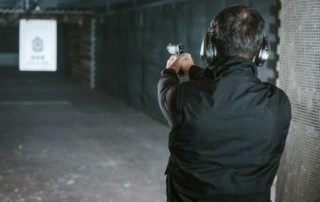 Rear view of man aiming gun at paper target