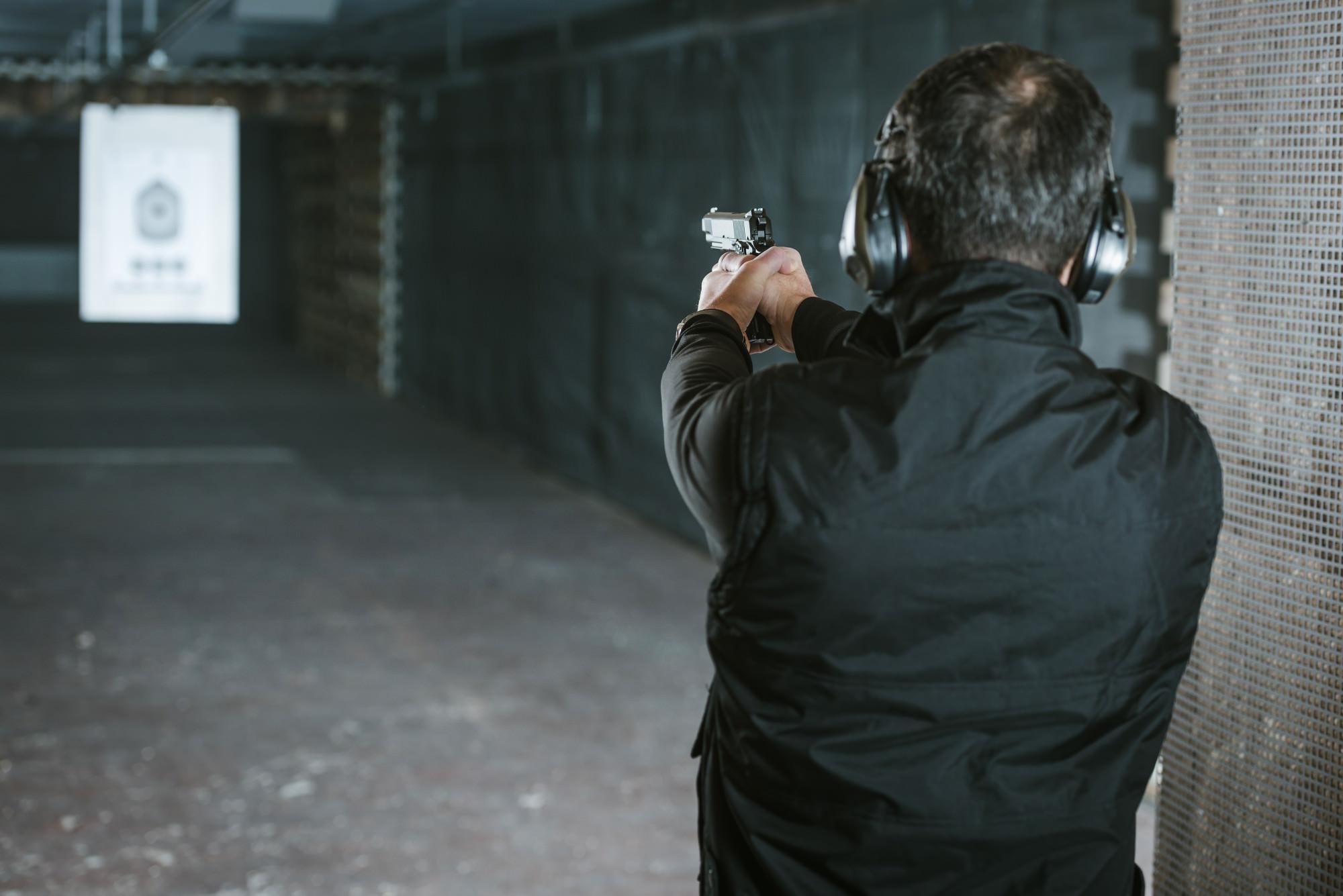 Rear view of man aiming gun at paper target